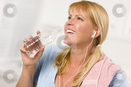 Pretty Blonde Woman with Towel Drinking From Water Bottle stock photo, Pretty Blonde Woman with Towel and Ear Phones Drinking From Water Bottle in Her Kitchen. by Andy Dean