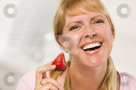 Pretty Smiling Blonde Woman Holding Strawberry stock photo, Pretty Smiling Blonde Woman Holding Strawberry in Her Kitchen. by Andy Dean