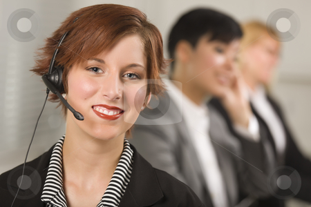 Pretty Red Haired Businesswoman with Headset and Colleagues stock photo, Pretty Red Haired Businesswoman with Headset and Colleagues Behind in Office Setting. by Andy Dean