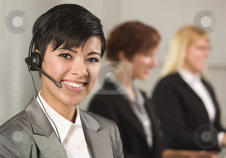 Pretty Hispanic Businesswoman with Colleagues Behind stock photo, Pretty Hispanic Businesswoman with Colleagues Behind in an Office Setting. by Andy Dean