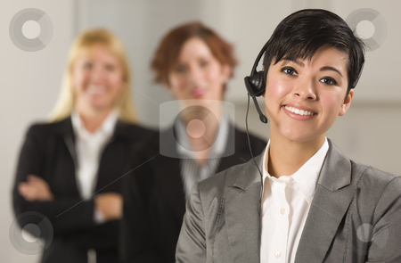 Pretty Hispanic Businesswoman with Colleagues Behind stock photo, Pretty Hispanic Businesswoman with Colleagues Behind in an Office Setting. by Andy Dean