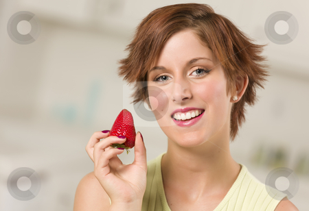 Pretty Red Haired Woman Holding Strawberry stock photo, Pretty Red Haired Woman Holding Strawberry in Her Kitchen. by Andy Dean