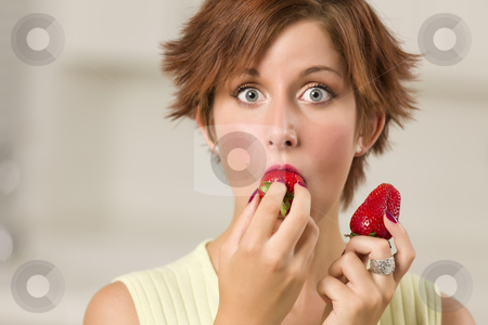 Pretty Wide-eyed Red Haired Woman Biting Strawberry stock photo, Pretty Wide-eyed Red Haired Woman Biting Strawberry in Her Kitchen. by Andy Dean