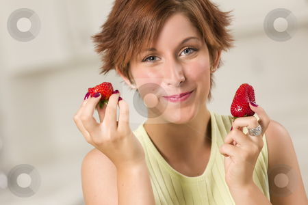 Pretty Red Haired Woman Eating Strawberry stock photo, Pretty Red Haired Woman Eating Strawberry in Her Kitchen. by Andy Dean