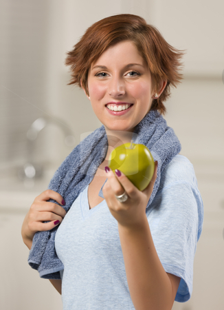 Pretty Red Haired Woman with Towel Holding Green Apple stock photo, Pretty Red Haired Woman with Towel Holding Green Apple in Her Kitchen. by Andy Dean