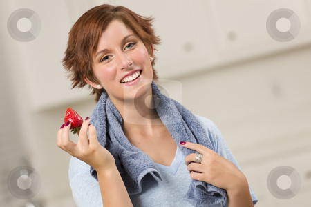 Pretty Red Haired Woman Holding Strawberry stock photo, Pretty Red Haired Woman with Towel Holding Strawberry in Her Kitchen. by Andy Dean