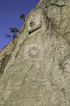 Buddha Carving stock photo, Ancient stone buddha carved into a hillside in Korea by elemery