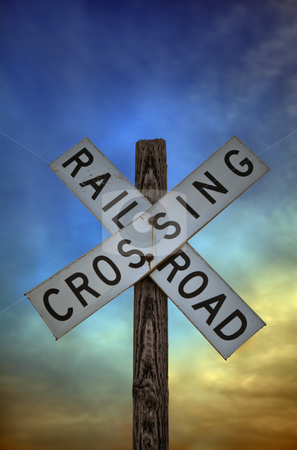Railroad Crossing Sign stock photo, A close up shot of an old railroad crossing sign against a beautiful sunset sky. by macropixel