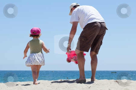 Father and daughter stock photo, Father having fun with his daughter on the beach. by Mariusz Jurgielewicz
