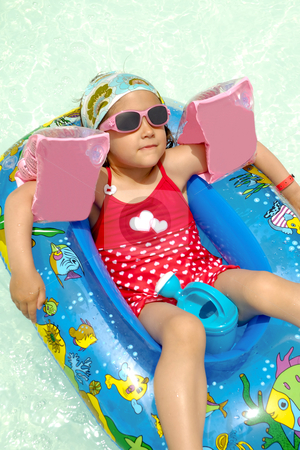 Child in pool stock photo, Young child is relaxing in boat in swimming pool. by Lars Christensen