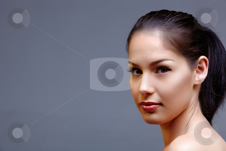 Beautiful natural woman stock photo, beautiful woman with long black hair in ponytail wearing classic natural make-up and beautiful skin texture over dark studio background with text space by lubavnel