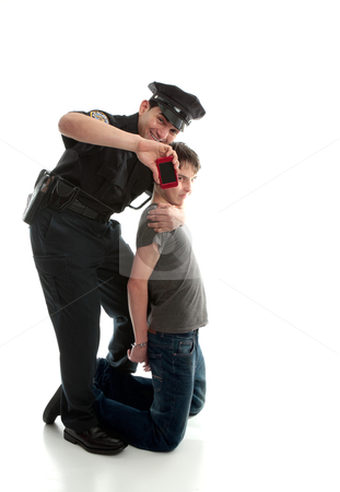 Happy policeman with apprehended teen boy stock photo, Happy policeman after arresting a teen felon and recovering stolen item. by Leah-Anne Thompson