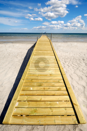 Bridge on beach stock photo, Long bridge on beach. The sky is blu with clouds. by Lars Christensen