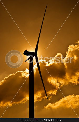 Wind turbine stock photo, Wind turbine in the back light of the sun with yellow sky and clouds. by Homydesign