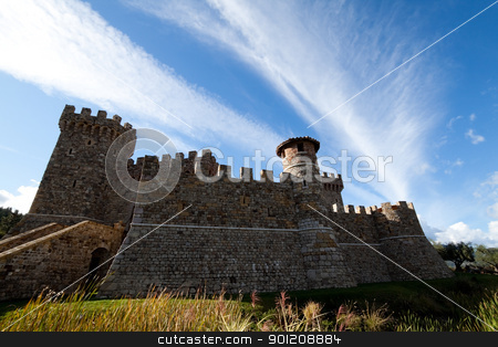 Castle Side stock photo, A stone castle with hilly mountains in the background by Kevin Tietz
