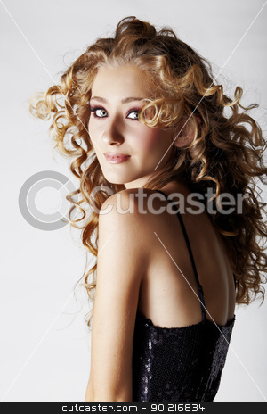 beautiful strawberry blond teenage girl . stock photo, beautiful strawberry blond teenage girl with green eyes and long curly hair blowing in wind over grey studio background . by lubavnel