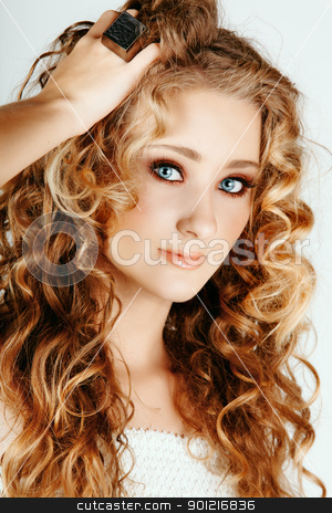 beautiful blond girl with curly hair stock photo, beautiful strawberry blond woman with blue eyes and long big curly hair with hand in hair by lubavnel