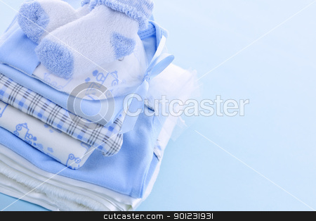 Baby boy clothes stock photo, Stack of boy infant clothing for baby shower on blue background by Elena Elisseeva