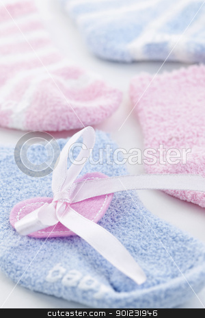 Baby socks gift stock photo, Pink and blue infant socks for baby shower with ribbon by Elena Elisseeva
