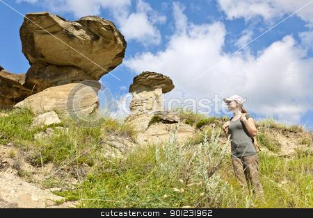 Hiker in badlands of Alberta, Canada stock photo, Young girl looking at hoodoos in badlands of Dinosaur provincial park, Alberta, Canada by Elena Elisseeva
