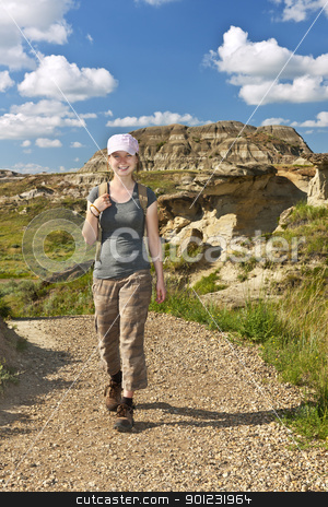 Hiker in badlands of Alberta, Canada stock photo, Smiling girl walking on path at the Badlands in Dinosaur provincial park, Alberta, Canada by Elena Elisseeva