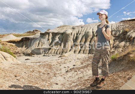 Hiker in badlands of Alberta, Canada stock photo, Smiling young girl standing at the Badlands in Dinosaur provincial park, Alberta, Canada by Elena Elisseeva