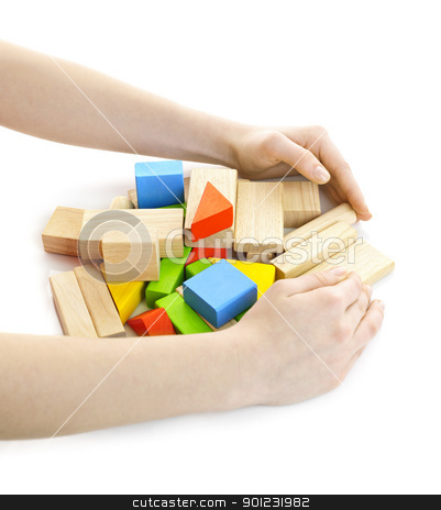 Hands with wooden block toys stock photo, Hands gathering pile of wooden block toys isolated on white by Elena Elisseeva