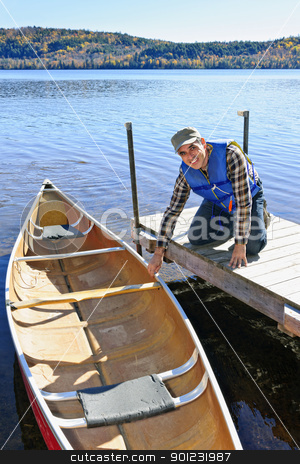 Man with canoe stock photo, Man holding canoe at dock on Lake of Two Rivers, Ontario, Canada by Elena Elisseeva