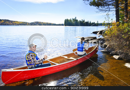 Canoeing near lake shore stock photo, Family in red canoe near rocky shore of Lake of Two Rivers, Ontario, Canada by Elena Elisseeva