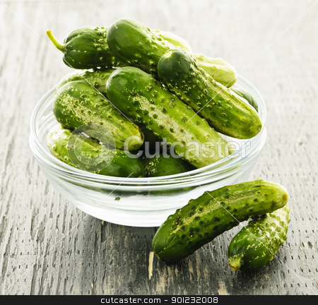 Small cucumbers in bowl stock photo, Fresh green pickling cucumbers in a glass bowl by Elena Elisseeva