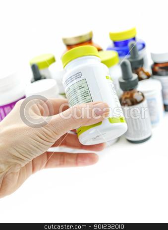 Hand holding medicine bottle stock photo, Hand holding medicine bottle to read label by Elena Elisseeva