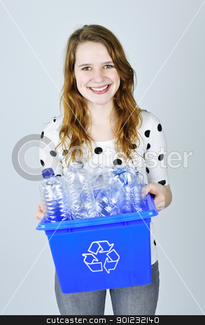 Young woman with recycling box stock photo, Smiling young woman carrying full recycling box on blue background by Elena Elisseeva