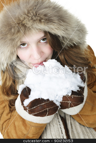 Playful winter girl holding snow stock photo, Playful young woman in winter coat with fur hood holding and tasting snow by Elena Elisseeva
