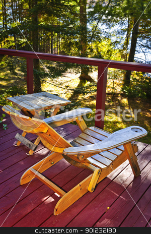 Chair on cottage deck stock photo, Wooden deck of cottage with lake view and Adirondack chair by Elena Elisseeva