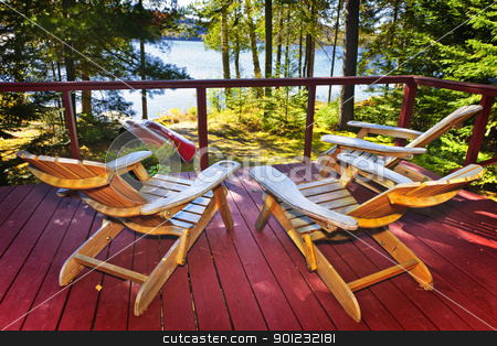 Forest cottage deck and chairs stock photo, Wooden deck of cottage with Adirondack chairs at lake by Elena Elisseeva