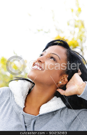 Smiling young woman outdoors looking up stock photo, Portrait of happy young black woman looking up outdoors in fall by Elena Elisseeva