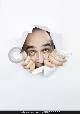 Scared face looking through hole in paper stock photo, Hole in paper with scared man looking through by Elena Elisseeva