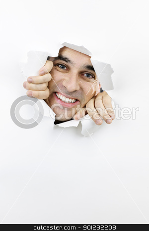 Happy face looking through hole in paper stock photo, Hole torn in paper with smiling man looking through by Elena Elisseeva