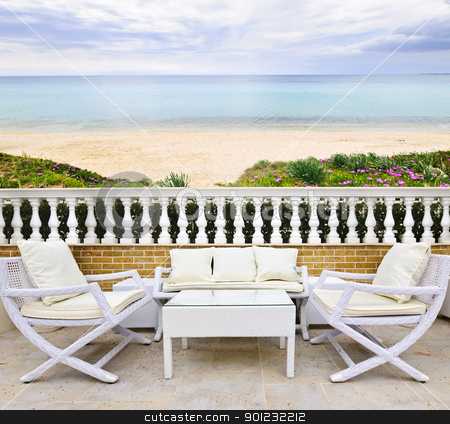 Patio with beach view stock photo, Patio with white wicker furniture with view of Mediterranean beach in Greece by Elena Elisseeva