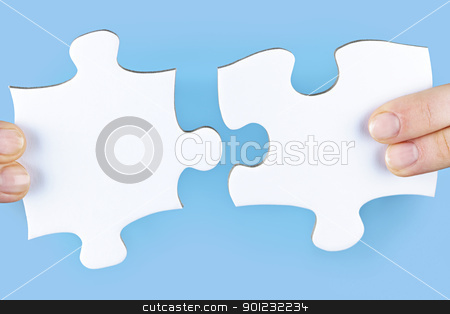 Fingers holding jigsaw puzzle pieces stock photo, Fingers joining large white blank jigsaw puzzle pieces by Elena Elisseeva
