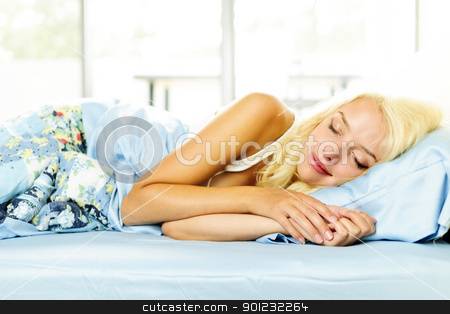 Woman sleeping in bed stock photo, Young woman peacefully asleep in bed in the morning by Elena Elisseeva
