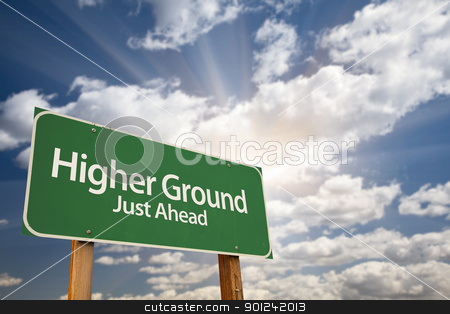 Higher Ground Green Road Sign stock photo, Higher Ground Green Road Sign Against Dramatic Sky, Clouds and Sunburst. by Andy Dean