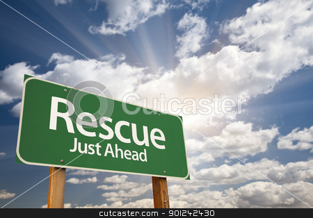 Rescue Green Road Sign stock photo, Rescue, Just Ahead Green Road Sign Over Dramatic Sky, Clouds and Sunburst. by Andy Dean
