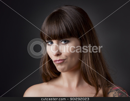 Sexy look stock photo, Beautiful young woman over a grey backround with a funny expression by ikostudio