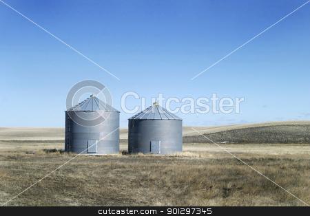 Two Steel Grain Bins stock photo, Two steel grain bins sitting on the prairie. by Tyler Olson