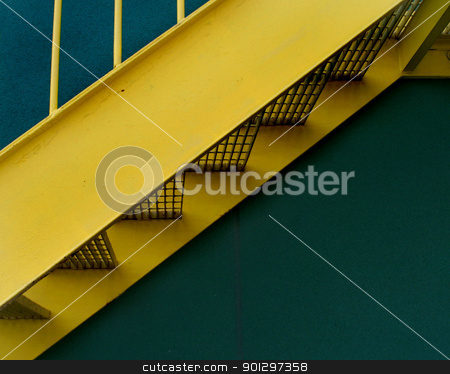 Yellow Staircase stock photo, A detail image of a yellow grated stairway infront of a green building by Tyler Olson