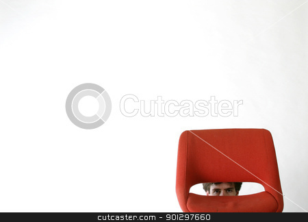 Shy Man stock photo, Shy man hiding behind a red chair. by Tyler Olson