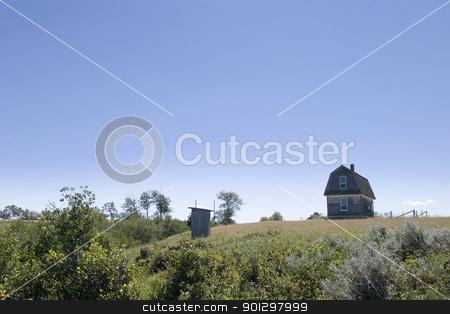 Prairie Homestead stock photo, An old prairie house on a grass meadow in Saskatchewan with an outhouse by Tyler Olson