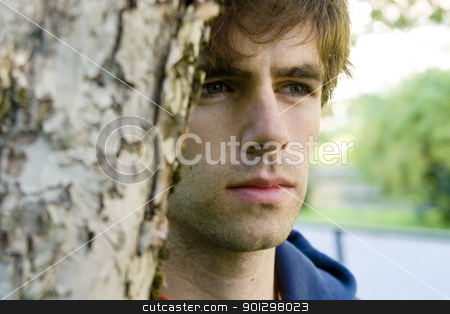 Thinking stock photo, A male standing near a tree thinking and looking off to the side by Tyler Olson