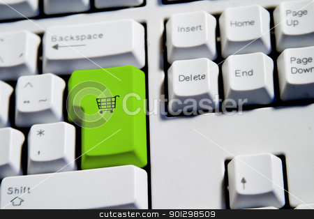 Shopping Cart stock photo, Computer Keyboard from a desktop computer with the enter key highlighted in green with a small shopping cart on it by Tyler Olson